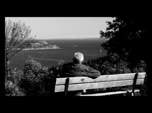 vieil assis sur un banc qui regarde la mer